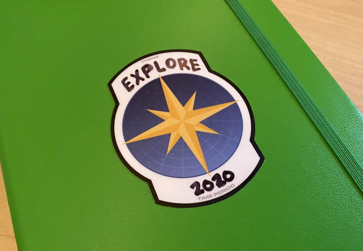 A photo of my journal with a sticker showing a compass and the theme Explore with 2020 below.